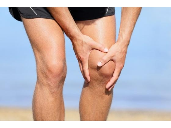 Man in shorts holding  obviously  painful knee