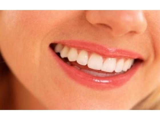 Woman smiling shoeing white healthy looking teeth and gums