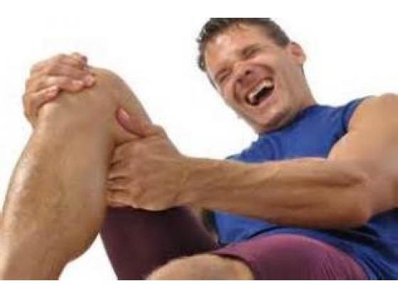 Man screaming in pain holding his leg