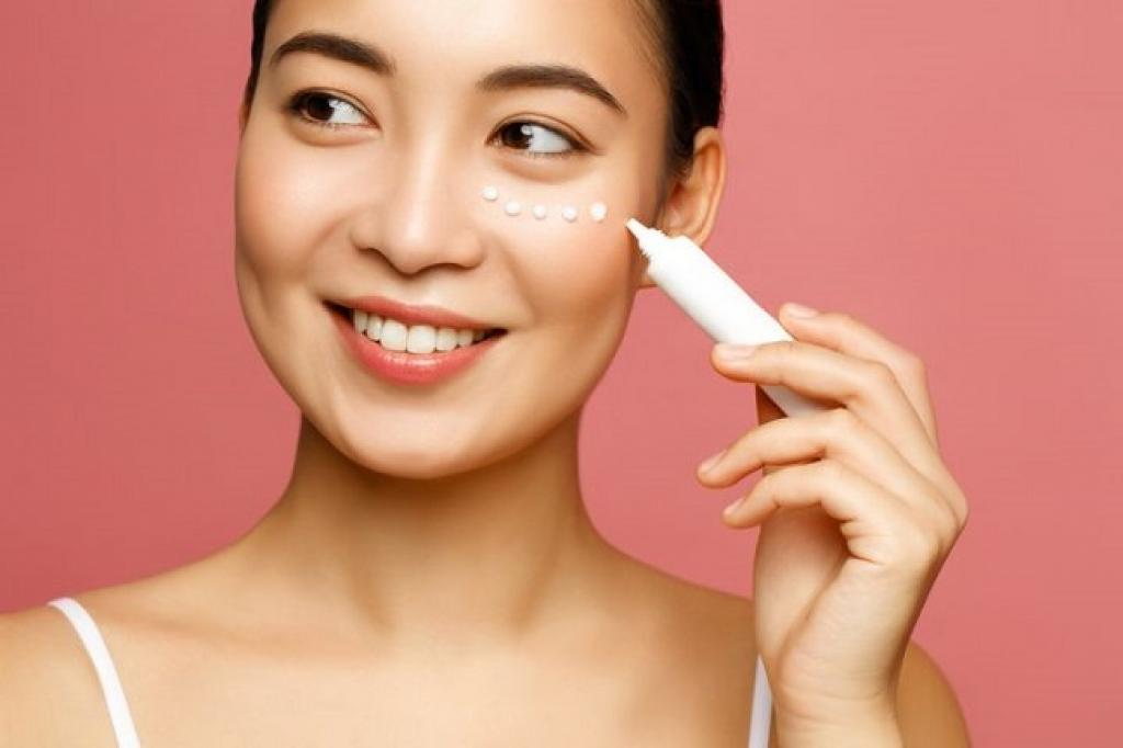Smiling girl putting cream on face