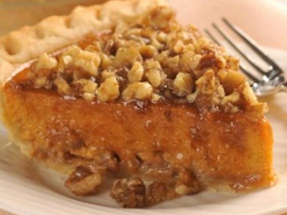 Slice of pumpkin walnut pie with graham cracker crust on a plate.