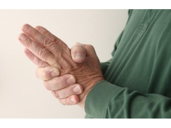 Woman experiencing neuropathy symptoms holding her hands to lessen the tingling sensation