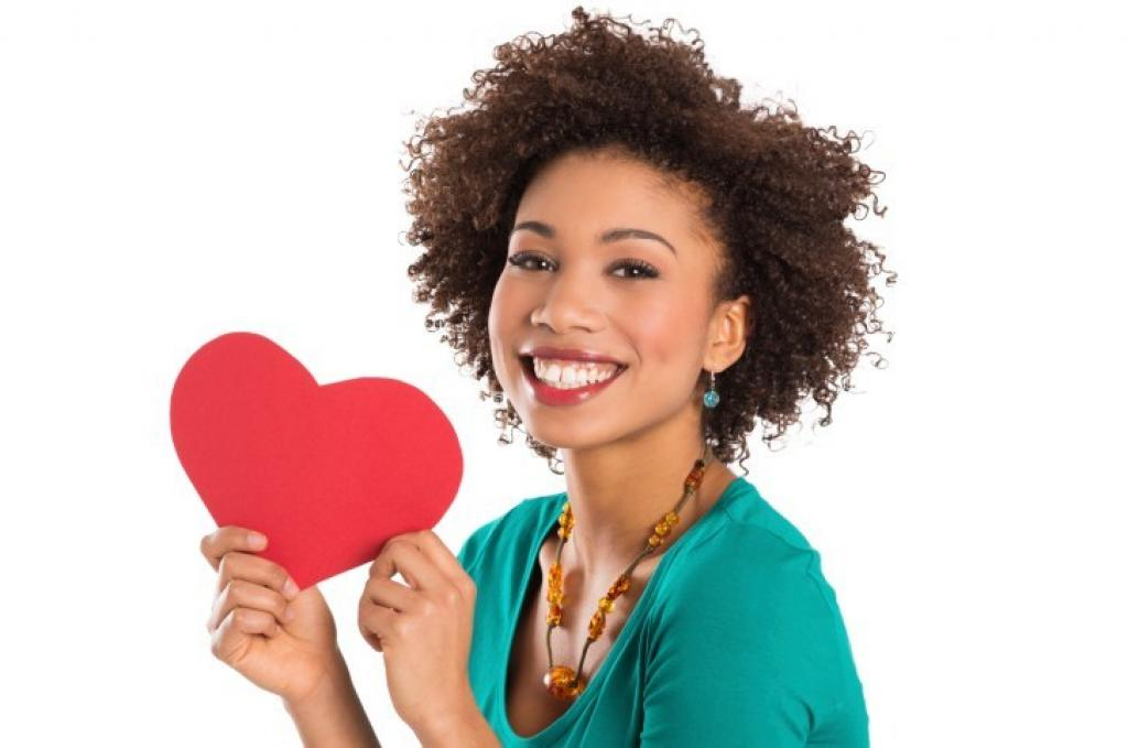 Young girl smiling and holding a healthy heart