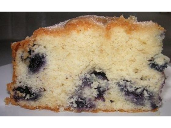 Large slice of sour cream coffee cake brimming with blueberries.