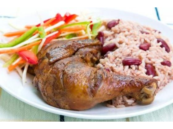 A plate of jerk chicken served over red bean & with julienne vegetables.
