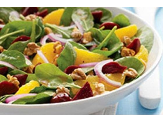 Bowl of baby spinach salad with citrus.