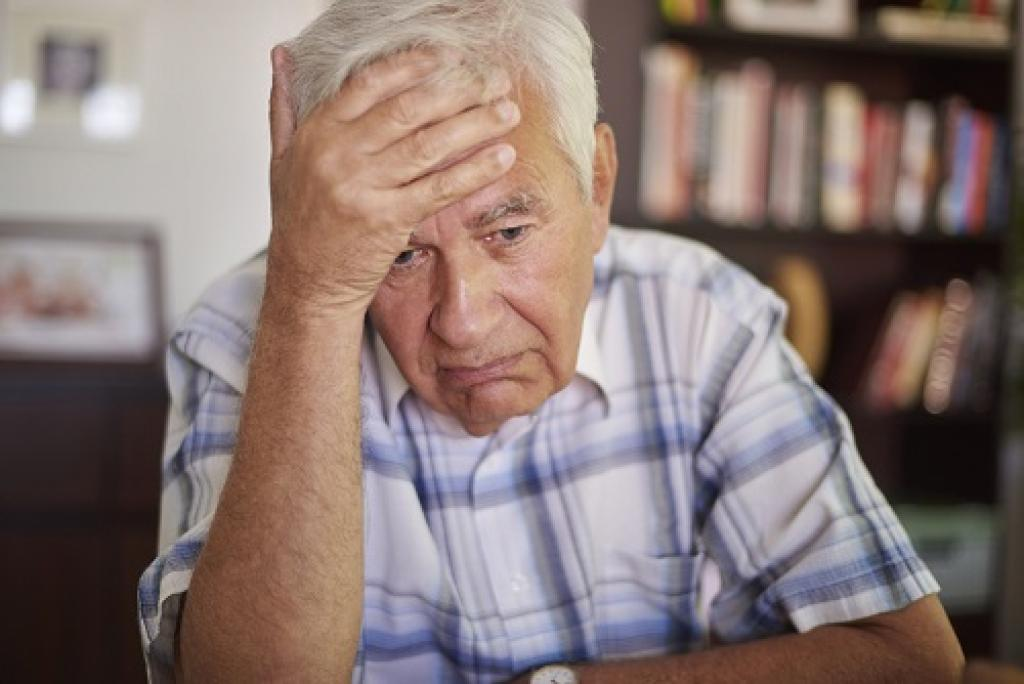 Senior man with his hand on his head looking dejected.