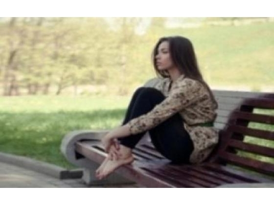 Lonely girl sitting on a bench