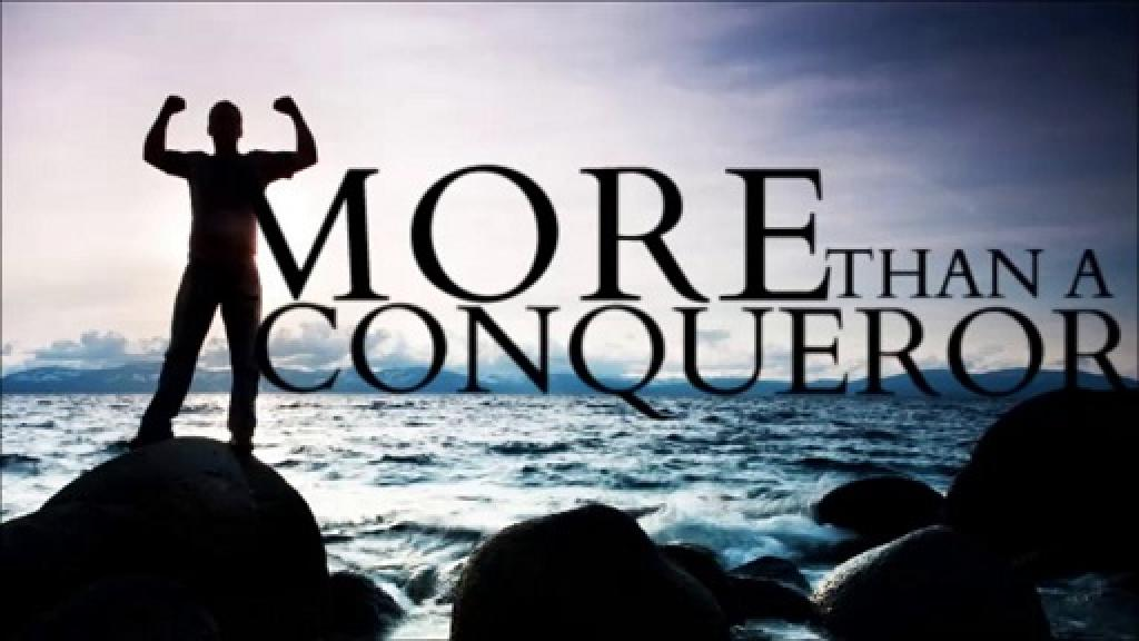 Man on mountain top with words more than conquerors.