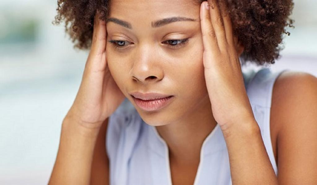 Young woman holding head with both hands looking worried and anxious