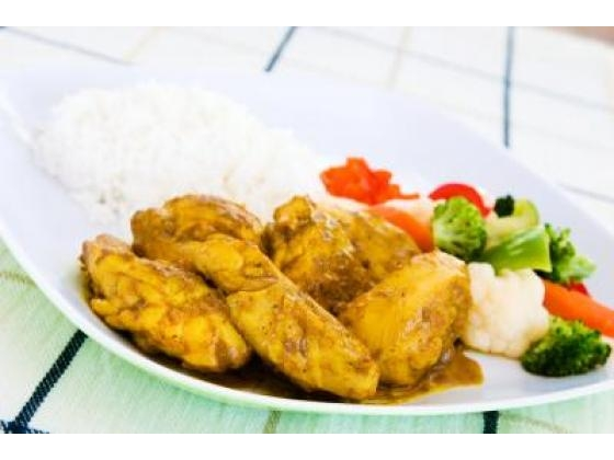 A curry chicken dinner plate with rice, olives and vegetables.
