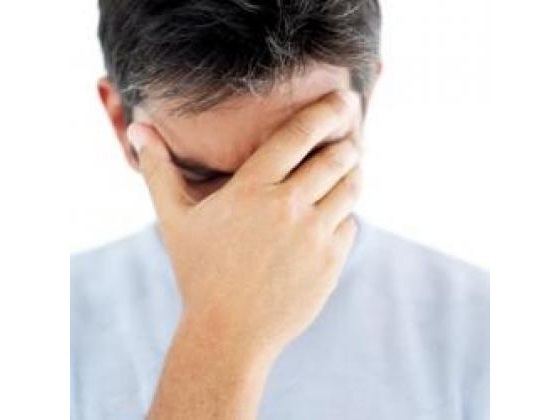Man holding forehead