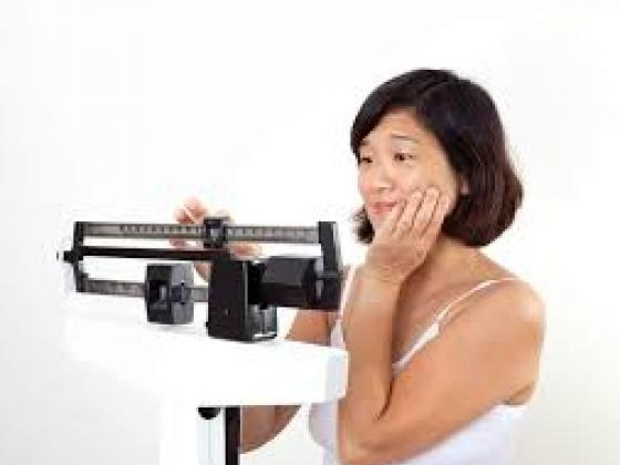 Woman standing on a scale and looking surprised
