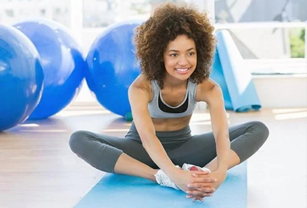 Smiling young girl on floor wit exercise balls