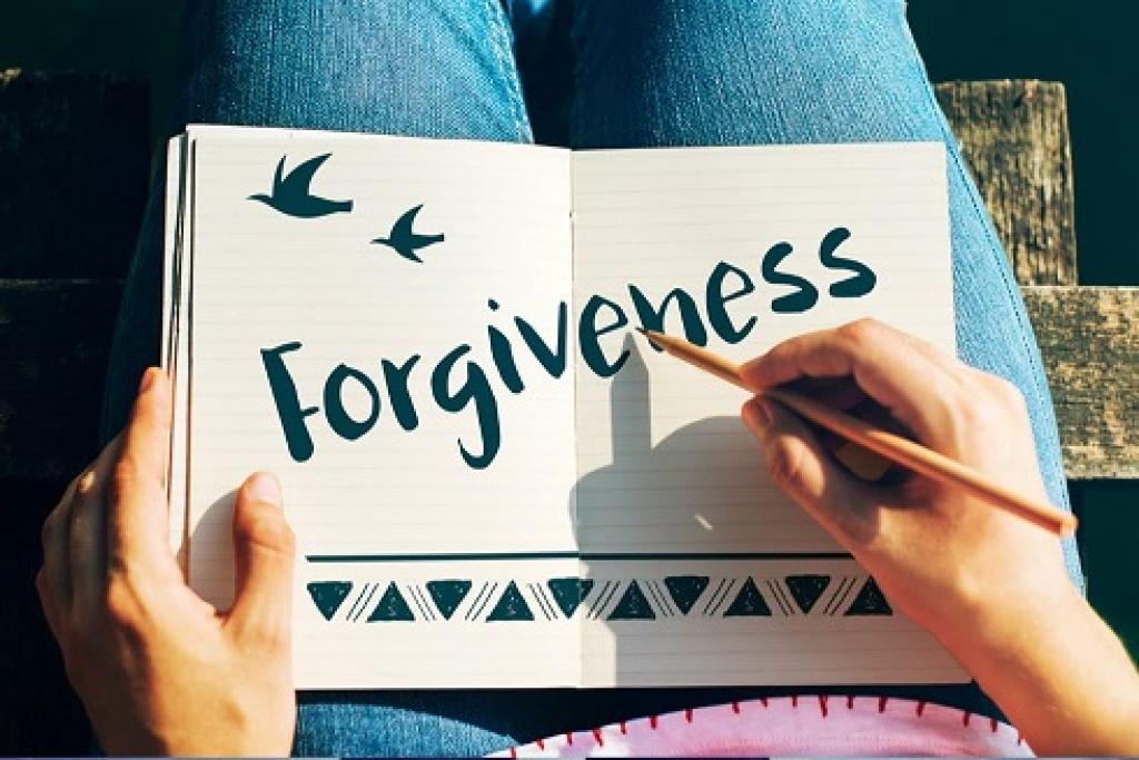 Young woman writing the word forgive on a pad