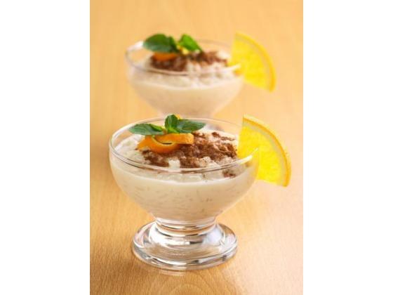 Two dessert glasses with rice pudding and orange garnish.