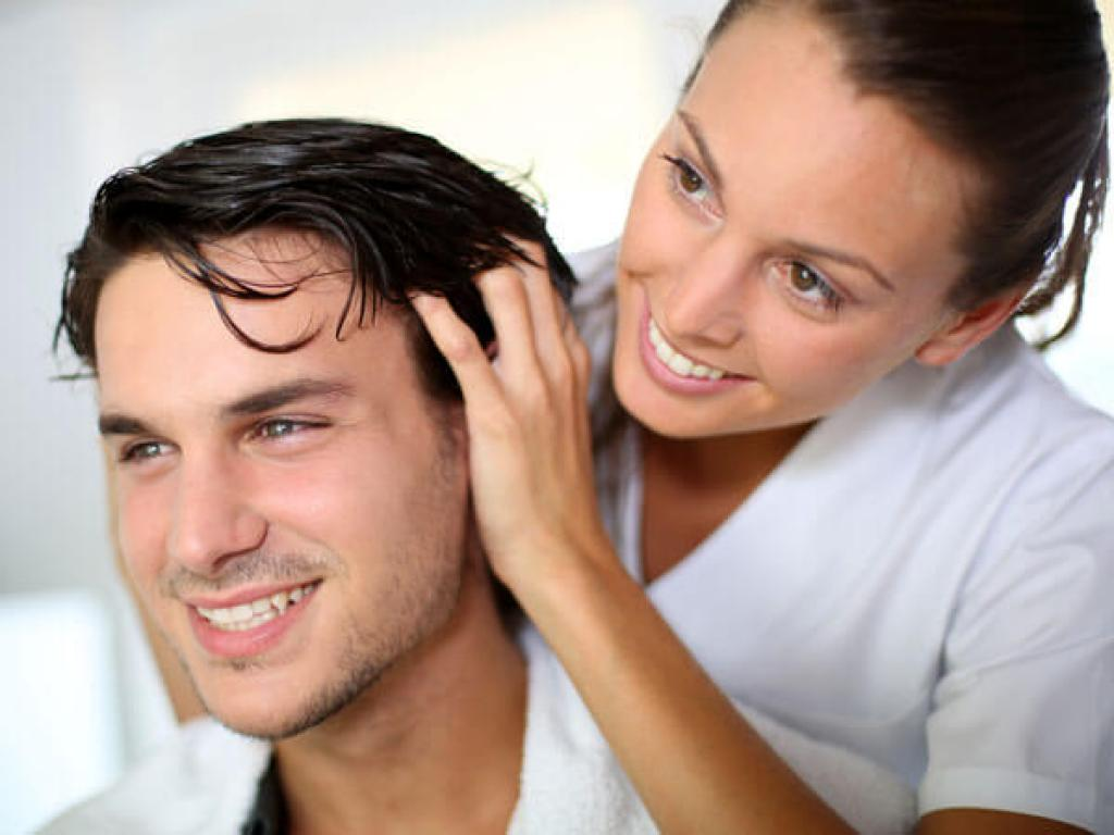 Woman caring for man's healthy head of hair