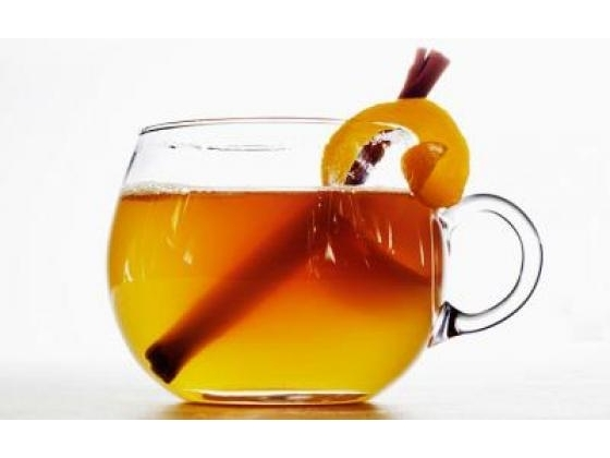 A hot toddy beverage with cinnamon and orange garnish.