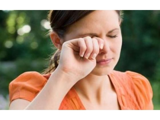 Woman rubbing sore eyes