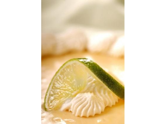 Slice of key lime pie with lime slice garnish.