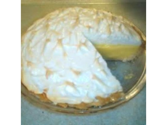A whole lemon meringue pie with a slice missing.