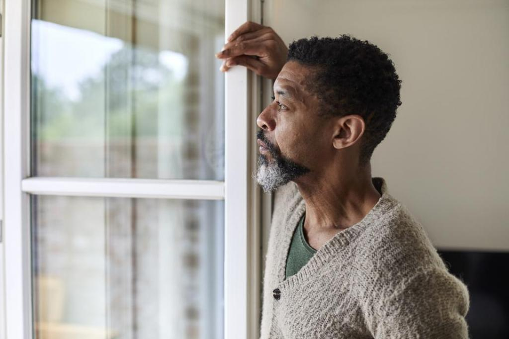 Man staring out the window looks sad and all alone