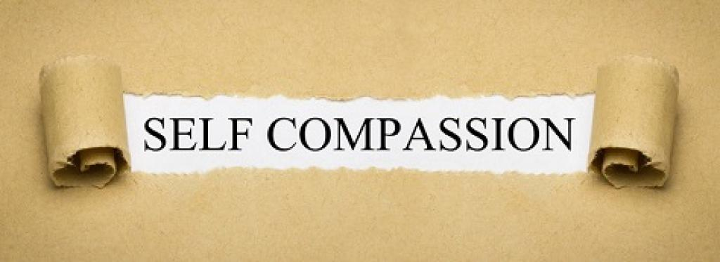 Self compassion written on a scroll