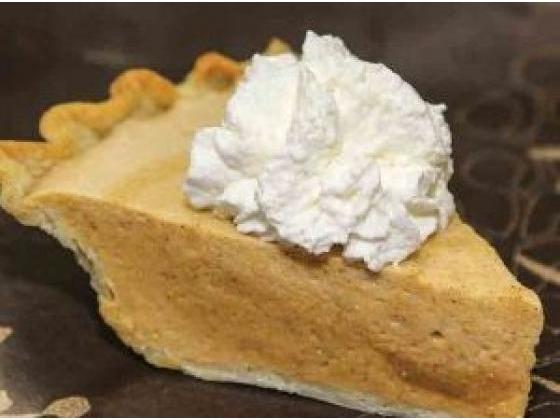 Slice of pumpkin chiffon pie with whipped cream.