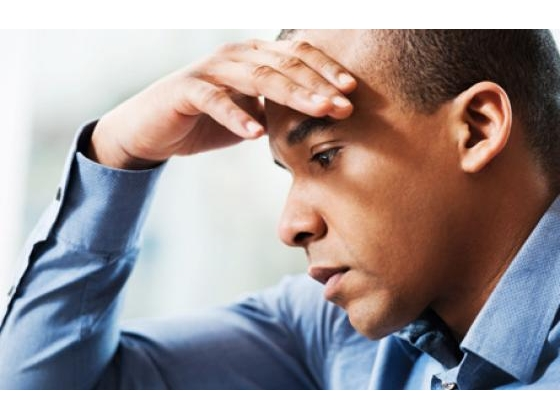 Distressed man with a hand on his forehead