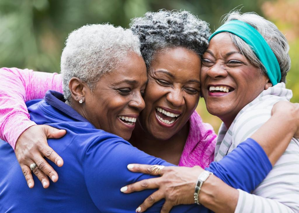 Three older women hugging and smiling in friendship