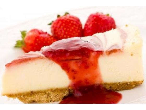 Strawberry cheesecake garnished with three strawberries and strawberry sauce.