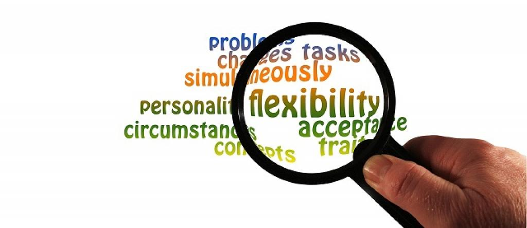 Hand with magnifying glass over the word flexibility