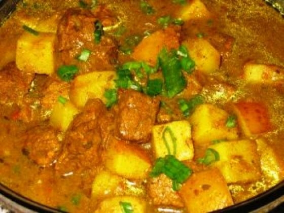A pot of curry chicken and potatoes simmering on the stove.