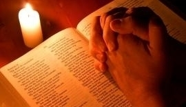 Hands praying on a bible.